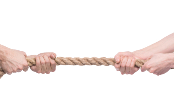 Tug-of-war. Two people pulling a rope in opposite direction isolated on white background.