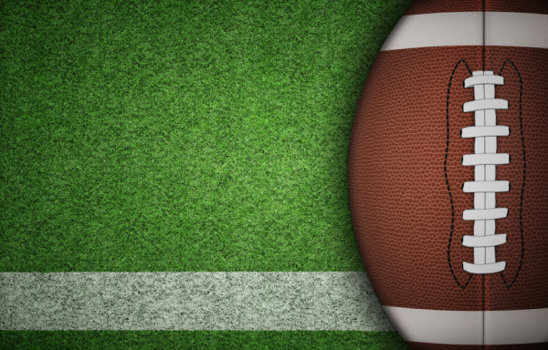American football ball on green grass