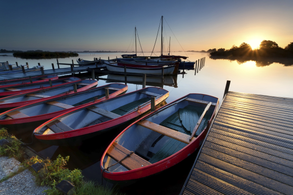 boats by pier at harbor during sunrise, Netherlands